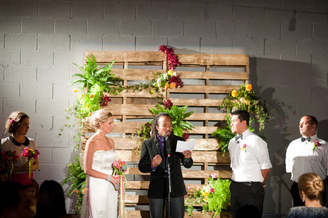 saying vows in front of wood pallet wedding alter