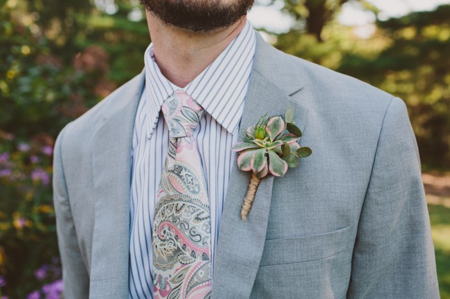groom with paisley tie and matching boutonniere