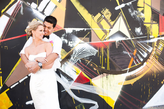 bride and groom against artistic painted wall