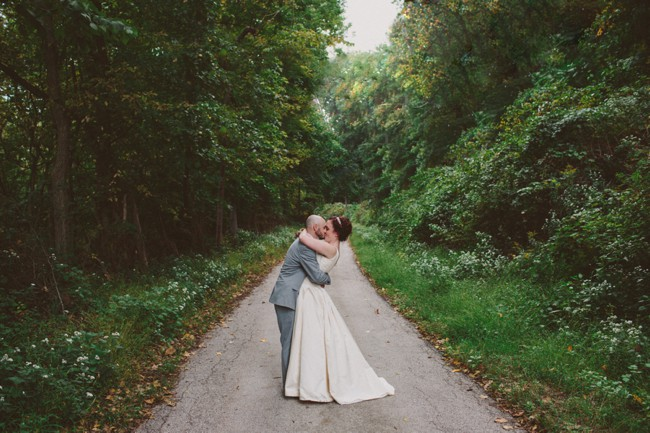 bride and groom embrace on a trail in the woods