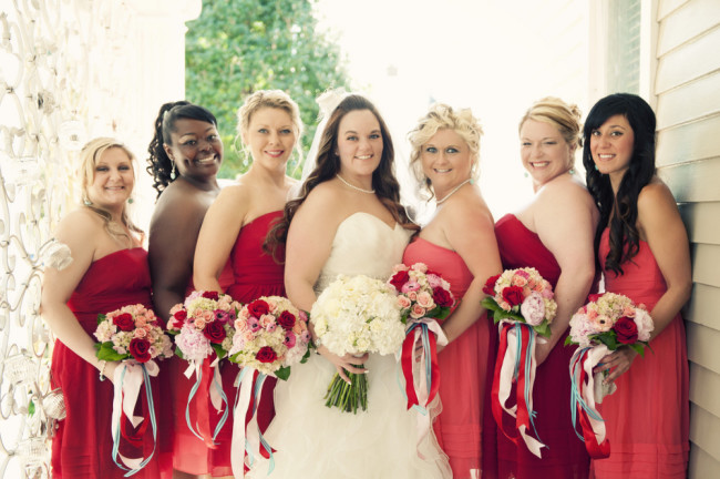 bride and bridesmaids in dark red and peach dresses holding bouquets