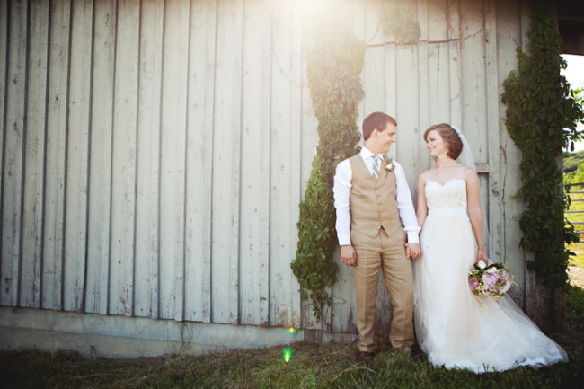 bride and groom hold hands next to wood barn house
