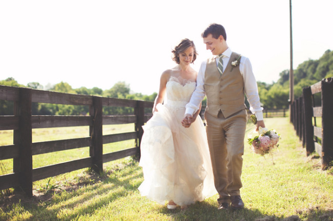 bride and groom walk along wooden fence on Tennessee farm