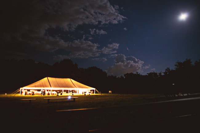 nigh photo of giant wedding tent with ligths and dark sky with moon