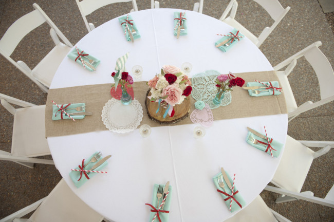 overhead photo of table setting with light aqua napkins and burlap table runner