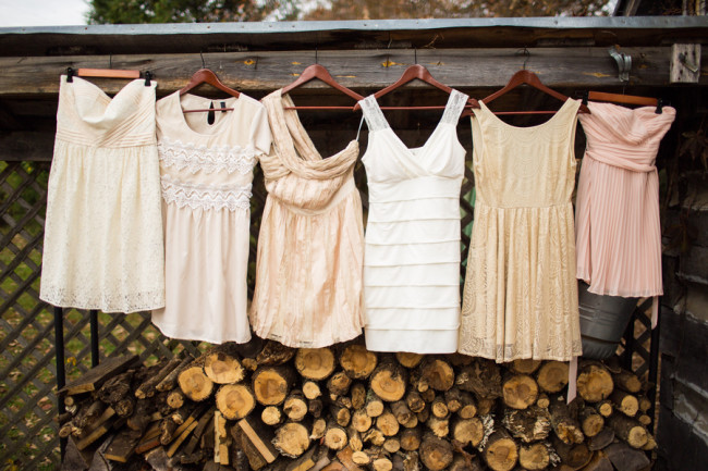 bridesmaid dresses hanging from wood log storage shed