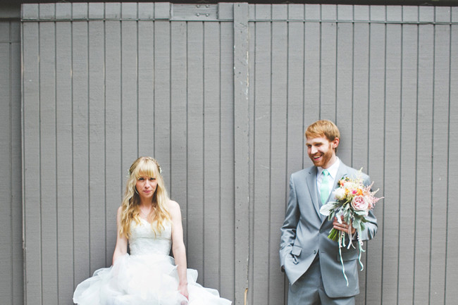 bride and groom against grey wooden wall