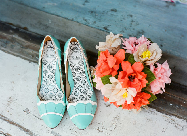 teal shoes next to colorful bouquet
