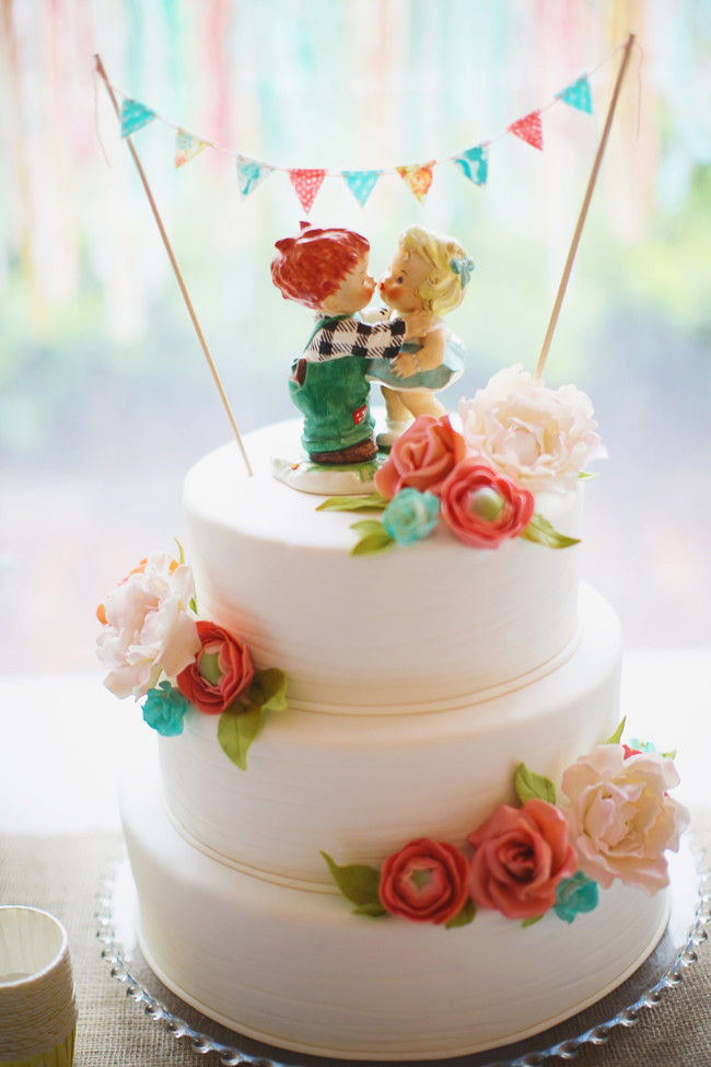 3-tiered wedding cake with whimsical figurine boy and girl cake toppers