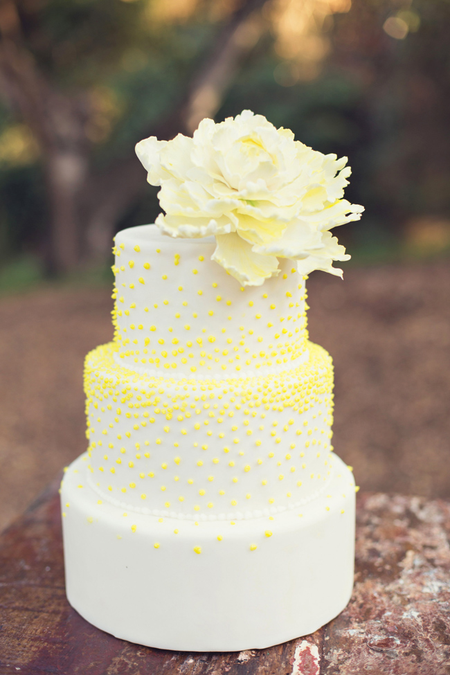 White 3-tier wedding cake with yellow dots and giant cream flower on top