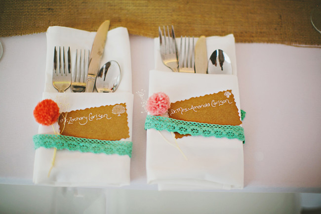 napkin holders with teal ribbon and cutlery