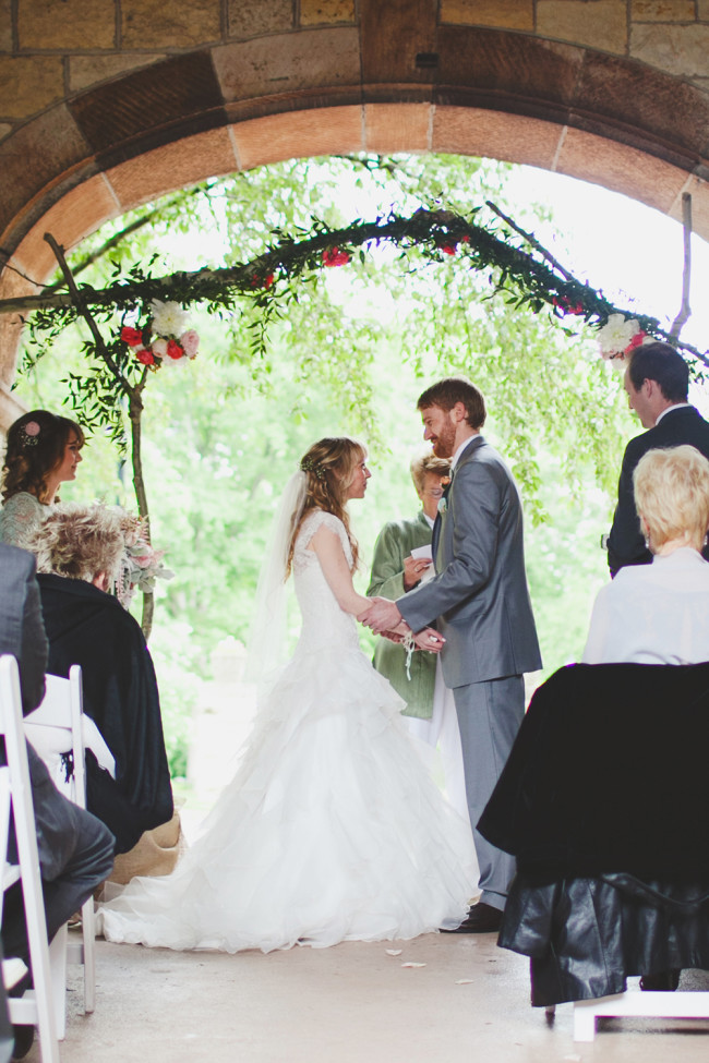 Bride and groom wedding ceremony at Ewing Manor with branch alter overhead