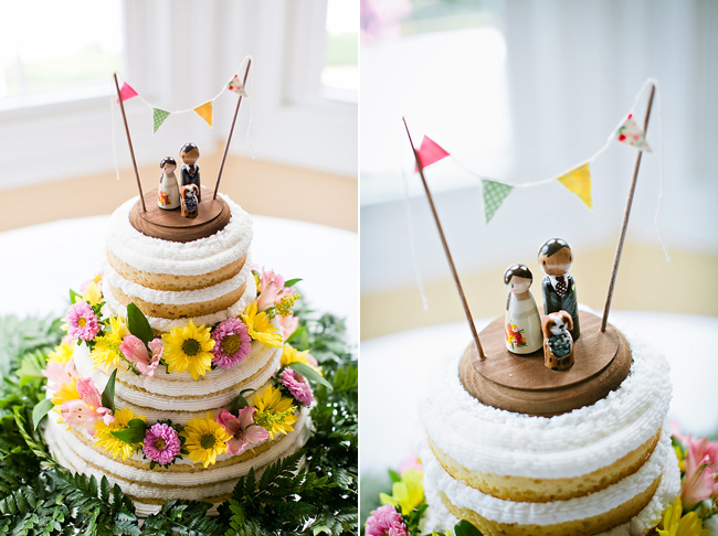 wedding cake with bunting cake topper and bride, groom, and dog figurines