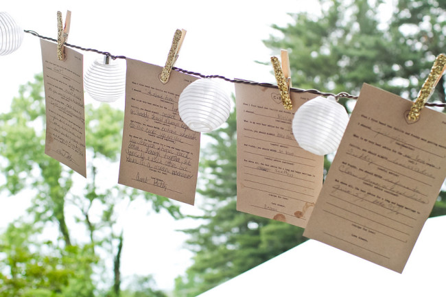 gold glitter clothespins and mini lanterns hang on wire at wedding reception