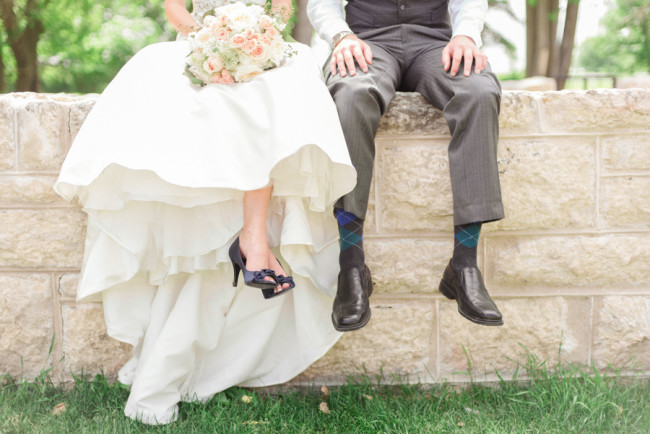 bride and groom sitting on stone wall displaying heels and argyle socks