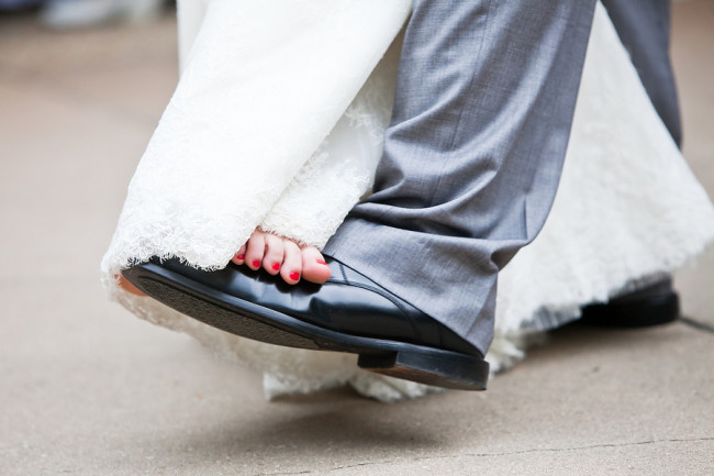 bride bare toes with red nailpolish on grooms black shoes
