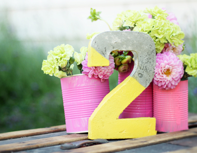 painted concrete table number with pink cans and flowers