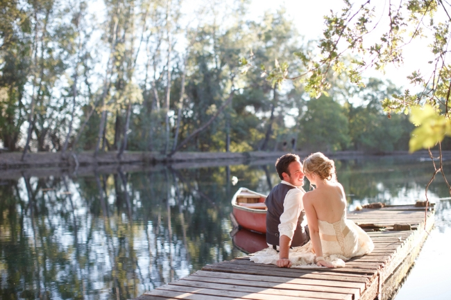 bride and groom on dock with canoe