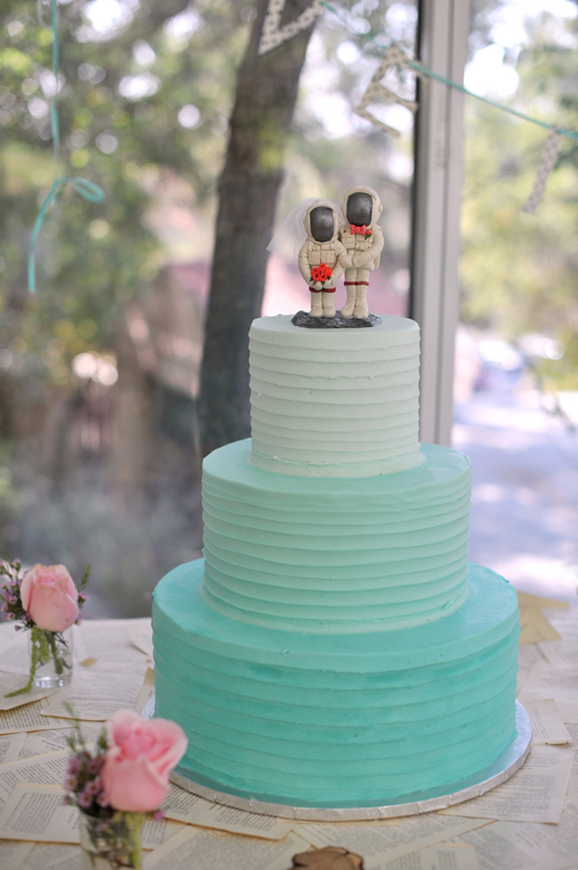 astronaut cake topper on light blue colored wedding cake