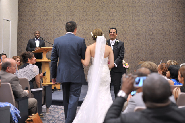 bride and groom walk to alter