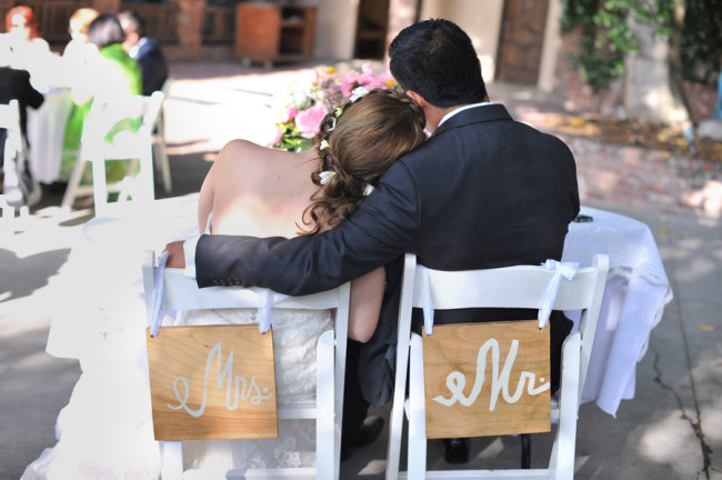 bride and groom sit on chairs with Mrs. and Mr. signs