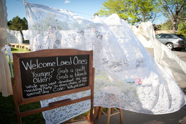 chalkboard sign with white sheets blowing in the wind at wedding reception in Los Angeles