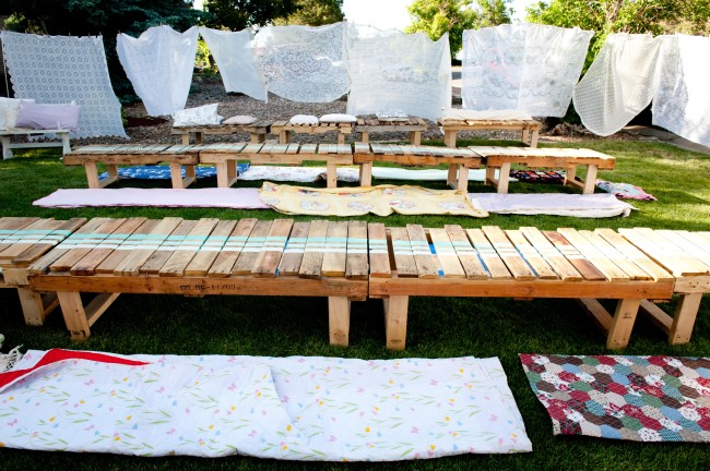 white sheets hanging on clothes line with food truck wedding reception wood plank tables and blankets on front lawn