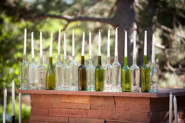 Row of empty wine bottles with white candles
