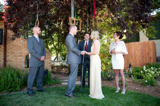 Bride and groom taking vows with picture frames hanging from tree behind them