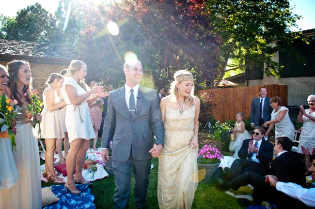 Bride and groom alk down aisle in backyard weddin ceremony in Los Angeles