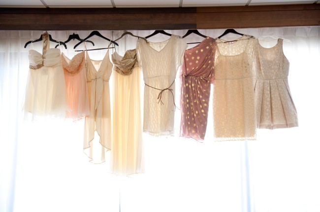 dresses hanging from beam in front of window