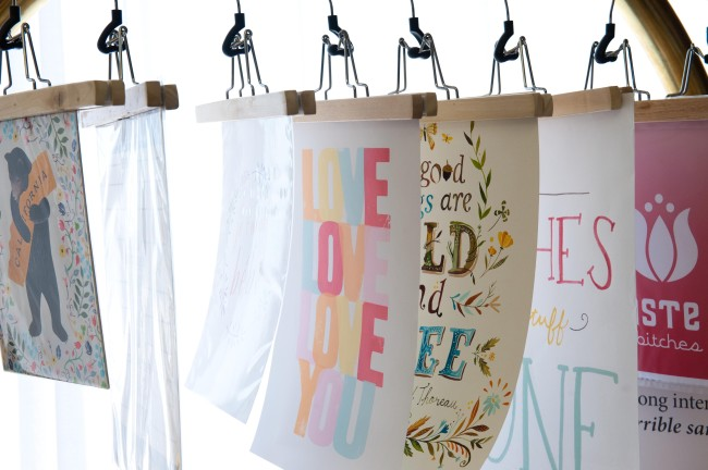 prints hanging from clothes hangers