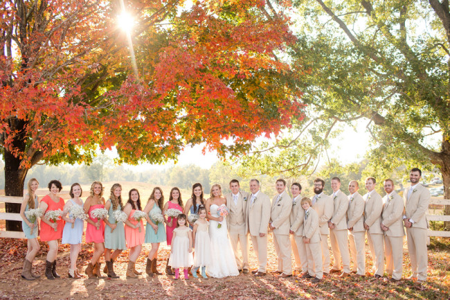 Fall Barn wedding - Bridal party standing in a row next to orange and red leaved tree