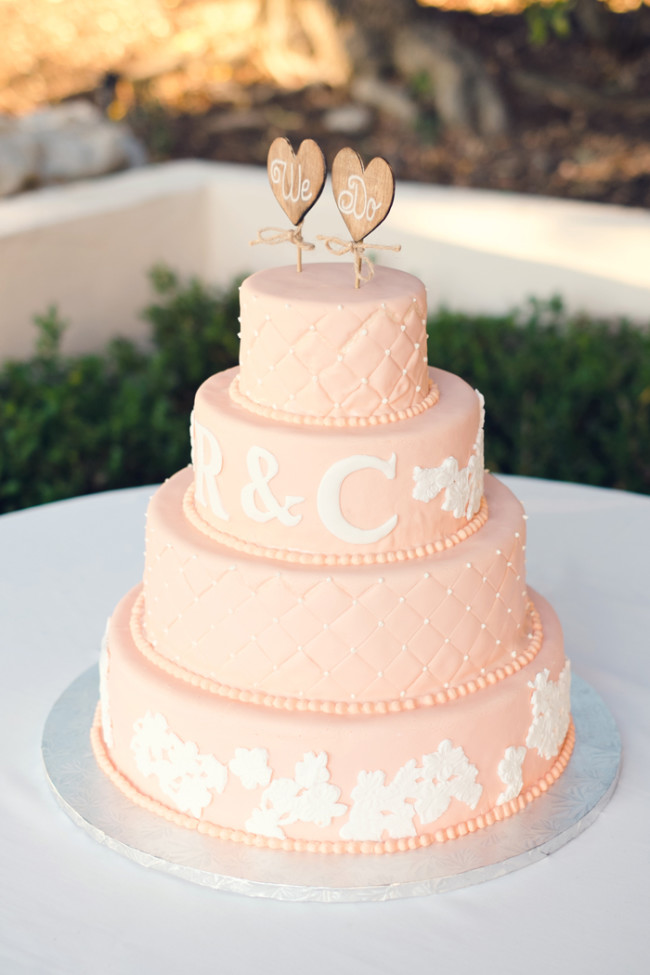 wedding cake with peach and ivory lace cutouts