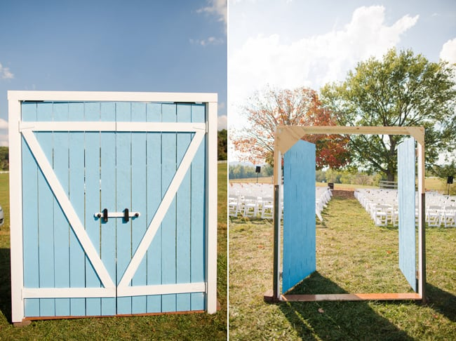 Blue barn door in middle of farm field opens to the ceremony seating area