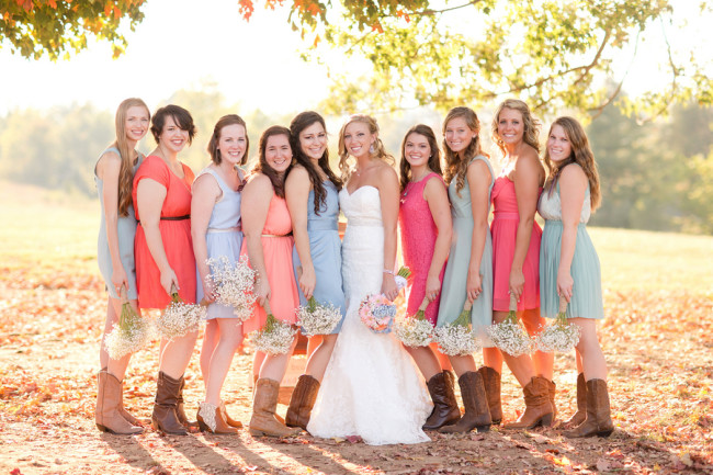 Bridesmaids in colorful dresses set against sunset and fall leaves