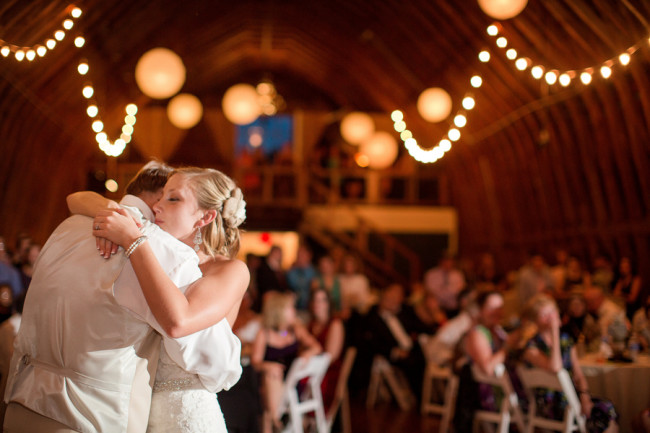 Fall Barn Wedding reception - bride and groom hug on stage