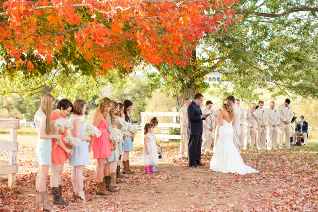Fall Barn wedding ceremony under large trees with leaves on the ground