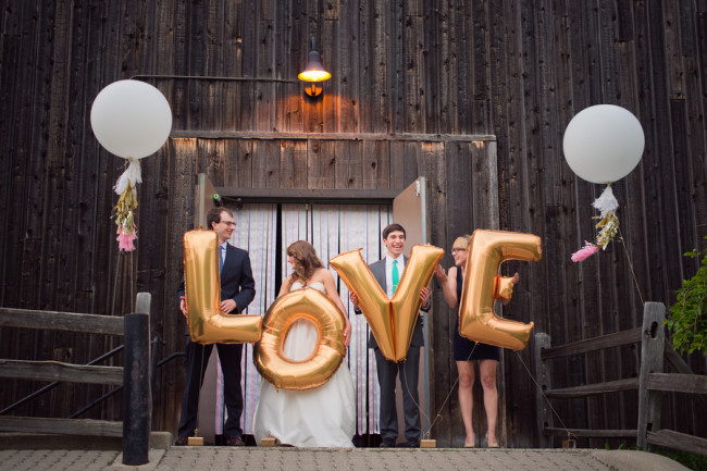 Bridal party hold giant letters that spell LOVE, standing in front of a barn