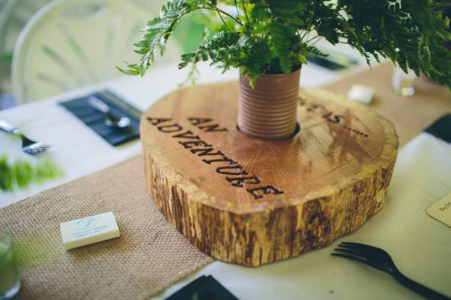 Wedding reception wooden slab centerpeice with love quote etched into the wood. Burlap table runner underneath.
