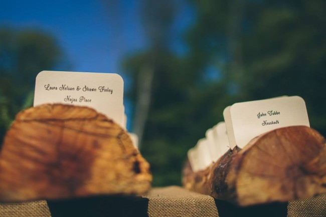 Handmade wooden wedding place card holders with white rounded piece of paper for name tag