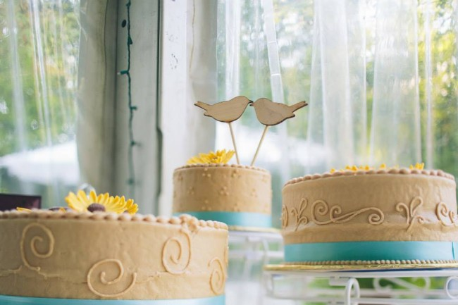 wood round themed wedding - Three round wedding cakes with sun flowers on top and teal blue ribbons around bottom with a love bird cake topper