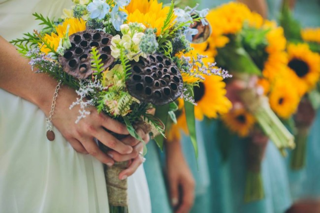 Yellow, blue, green, brown bridesmaids bouquets with sun flowers and dried lotus pods