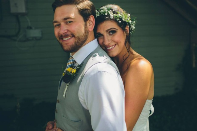 Bride hugging groom from behind wearing a baby's breath bouquet flower crown and groom weaing a grey vest with a yellow flower boutonniere