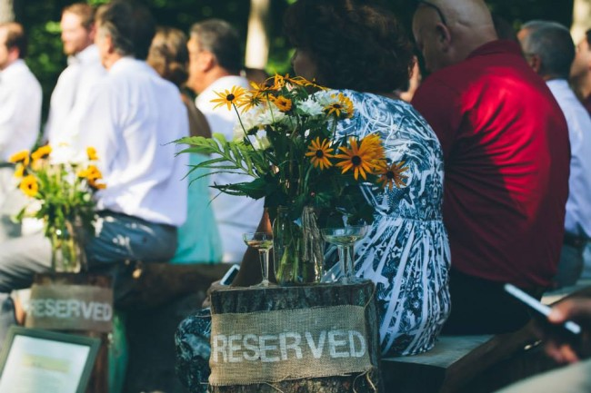 Wedding ceremony guests sitting on handmade wooden bencehes with a wood stump and a reserved sign made out of burlap with yellow and brown Black-eyed Susan flowrs in clear vase