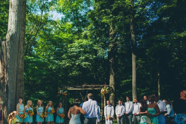 Bride with father standing at wooden arbour during wedding ceremony. Bridesmaids wearing ligh blue dresses and carrying sun flowers. Grooms men wearing suspenders and bow ties.