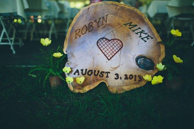 Wood round themed wedding slab with bride and groom's name etches into it with a heart and wedding date. Handmade yellow paper flowers surrounding the wood round.