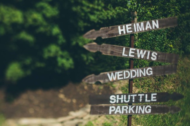 Wooden wedding sign with arrows pointing to certain areas with write writting
