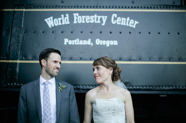 bride and groom stand in front of sign for World Forestry Center in Portland, Oregon
