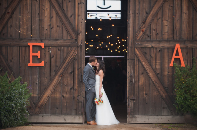 bride and groom kiss in barn doorway with giant letters E and A on wood doors